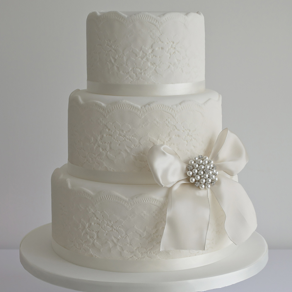 Lace wedding cake with vintage brooch accent. Cake by Sugar Ruffles, Rampside, UK.