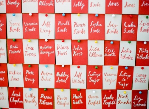 Red and white escort cards pinned in a checkerboard pattern. Featured on weddingomania.