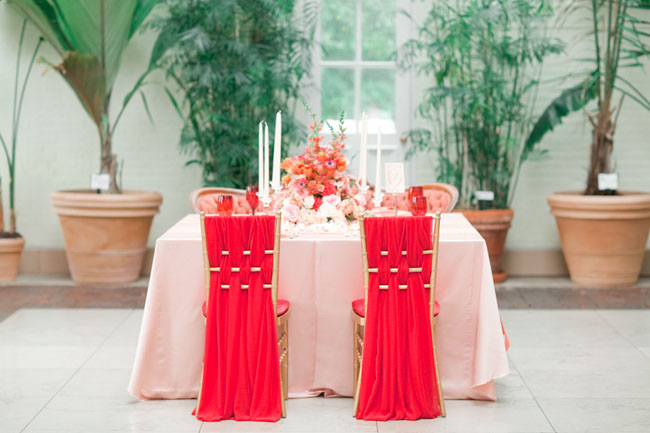 Bright red chiffon woven around the backs of clear acrylic chiavari chairs. Design by Events Luxe, photo by Jordan Brittley, featured on Green Wedding Shoes.