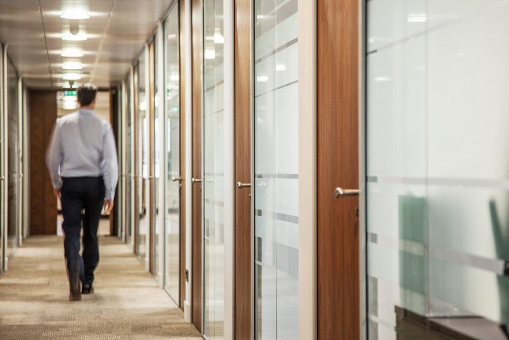 Man walking down office corridor