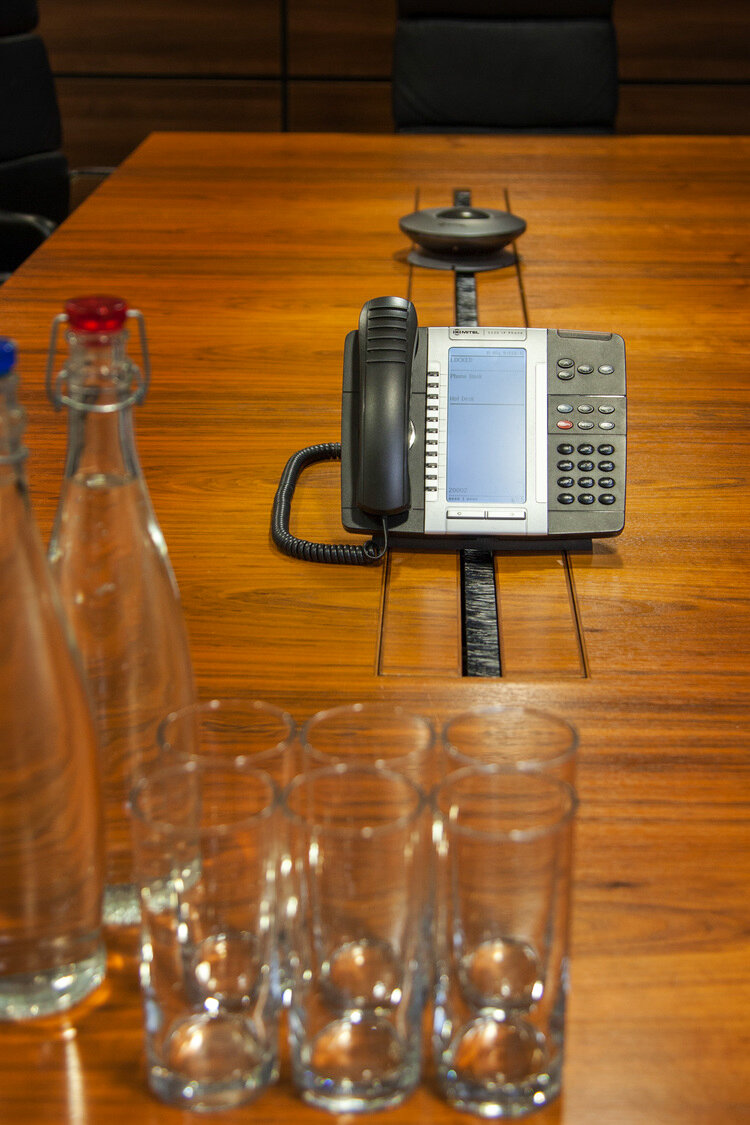 Boardroom table with water glasses and phone