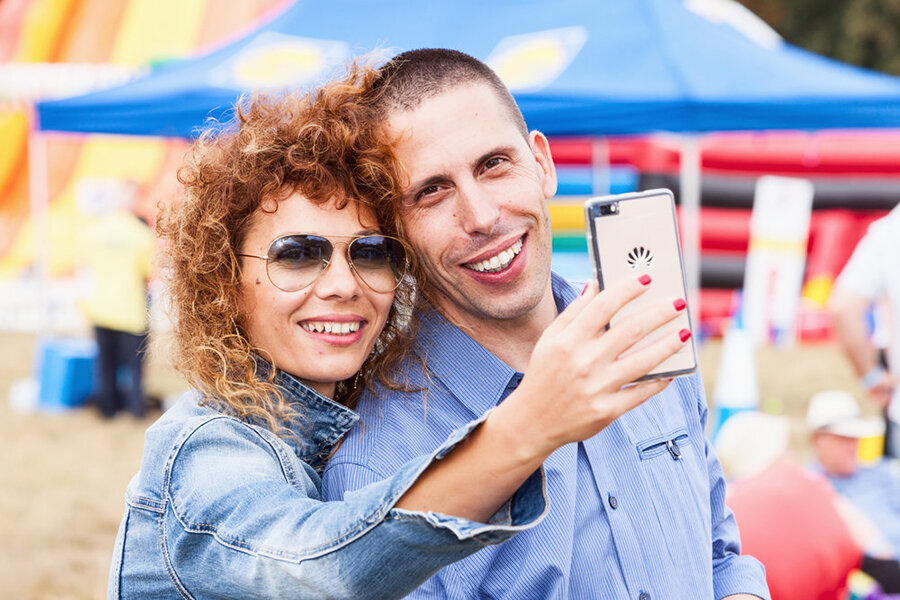 A couple look to camera smiling taking selfie