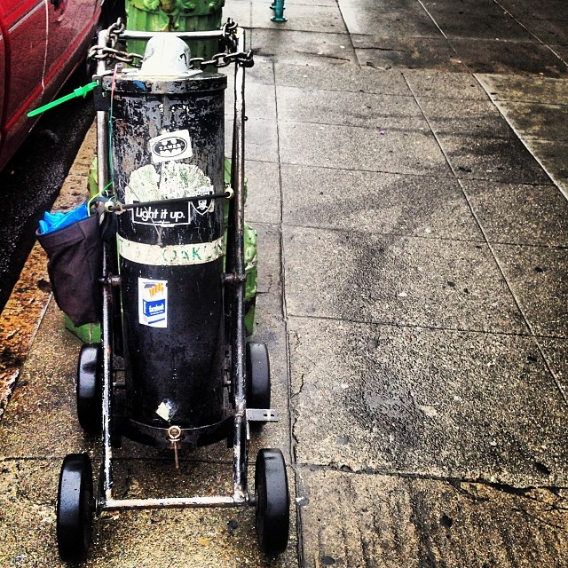 Hopper for collecting coins from parking meter, chained to a lamppost. #2milesoftelegraph