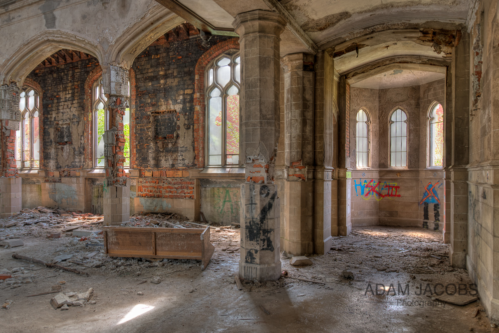 A view of the inside of St Agnes Church, Detroit where one can clearly see where the floor has broken up and valuable tiling stripped from the walls and pillars by scrappers.