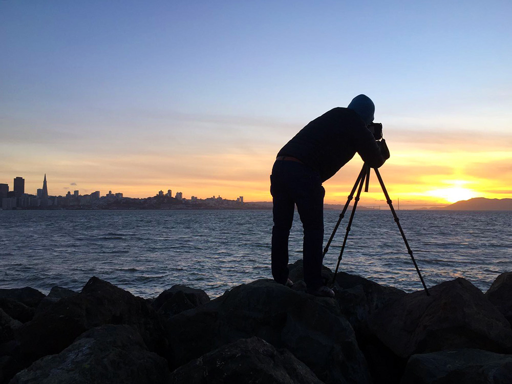 Photographer Adam Jacobs photographing The Golden Gate Bridge in San Francisco California at Sunset.