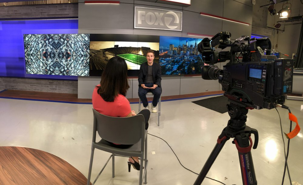 Adam Jacobs being interviewed inside the Fox Studios with his fine-art photographs on display.
