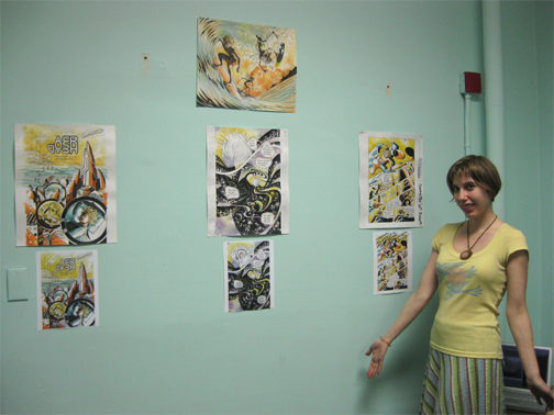 mindy indy is standing next to 4 pieces of her original AER HEAD comic art.