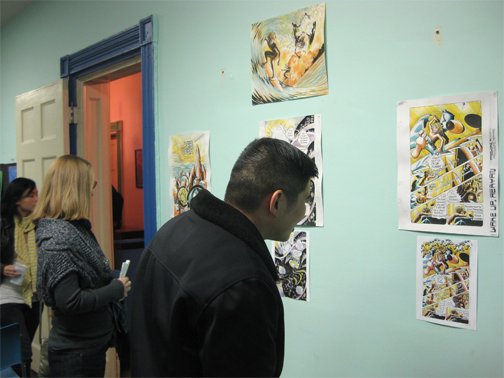 People looking at mindy indy's AER HEAD comic art on the wall.