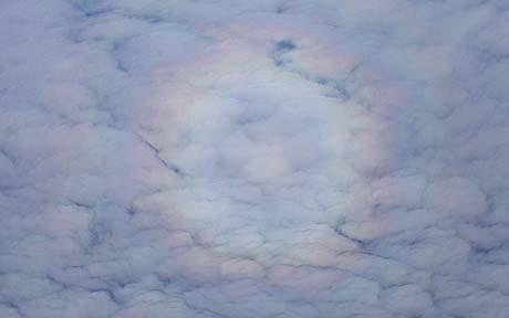 Circular rainbow as seen from above the clouds on a plane.