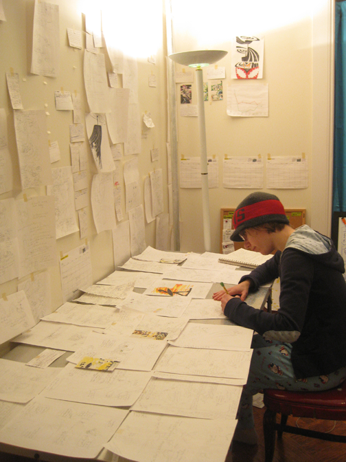 mindy indy is drawing at her studio with many pages covering her whole table.