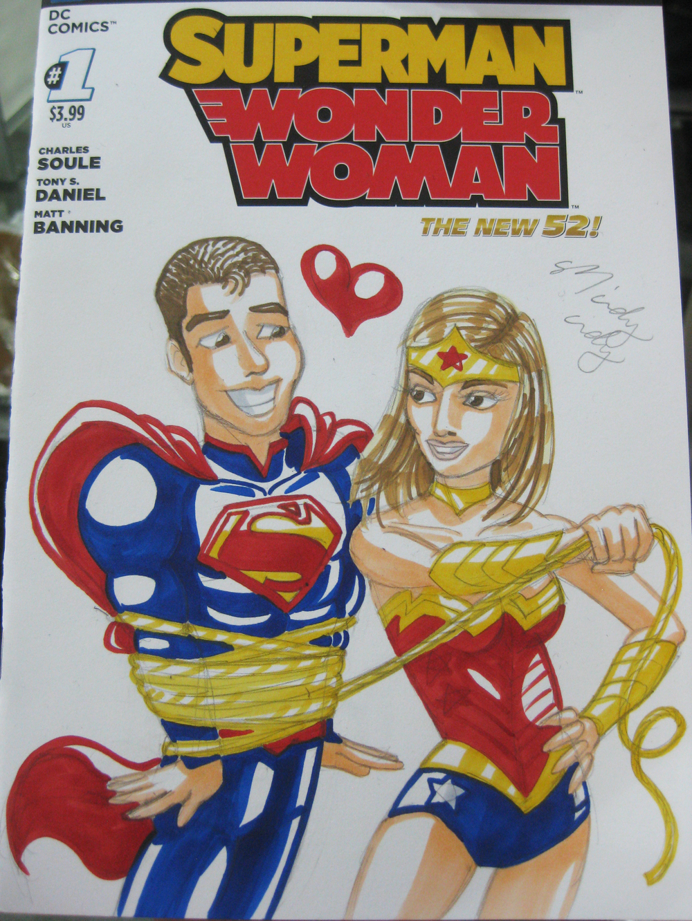 "One cool thing about NYCC is that Marvel and DC make special blank covers for some comics for artists to draw on!  All this guy said was ""draw me as Super Man and my wife as Wonder Woman.""  This is the quirky kind of drawing you get :)  He was like ""OMG that's just like my marriage!!""  haha, Mindy Indy knows... :)"