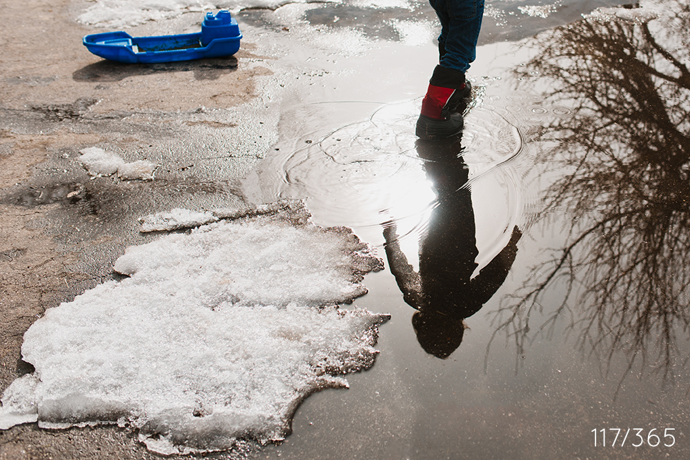You were playing in the giant snow puddle by the garage with your blue boat.