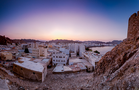 An 8 stitch panorama of the corniche from Mutrah Fort with the sun setting behind the Hajar mountains