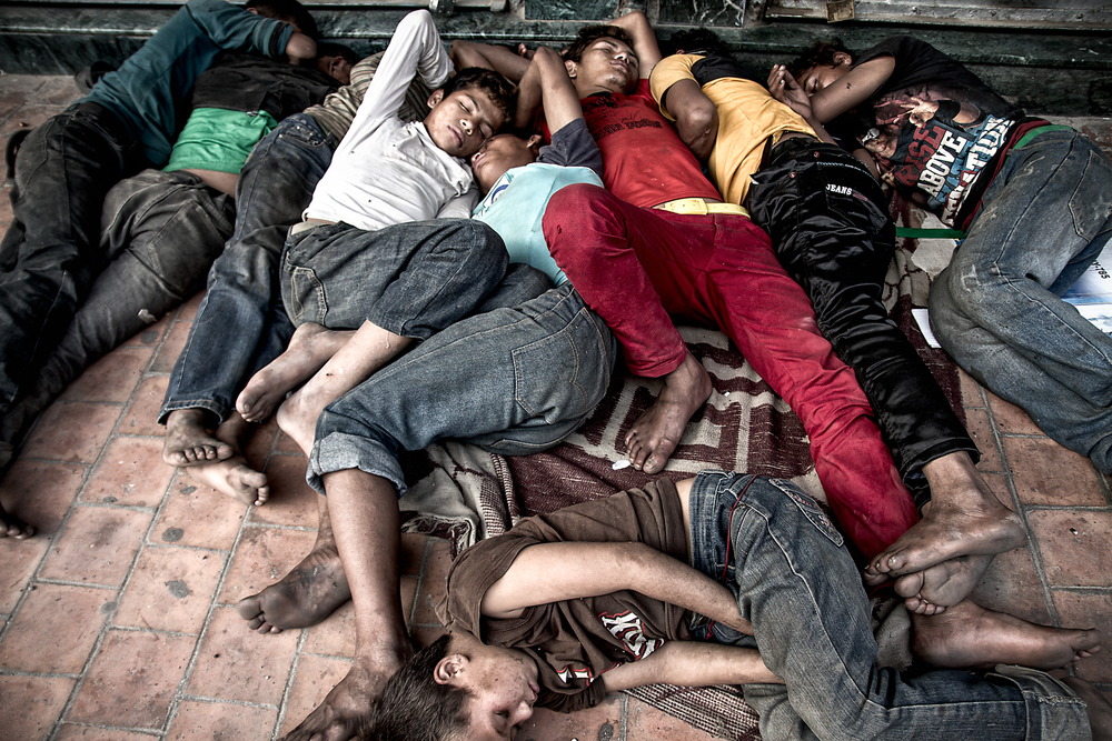 Sadly, unclean and hungry the boys sleep cold and bare to the dirty streets of Kathmandu.  Note the youngest boy has the worst position, at the gangs' feet.