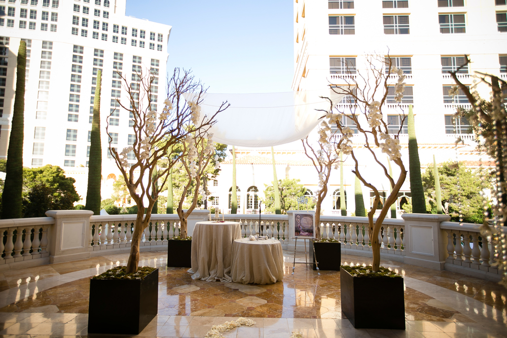 Sand blasted manzanita branches create a custom chuppah for the interfaith wedding ceremony at Bellagio Las Vegas.