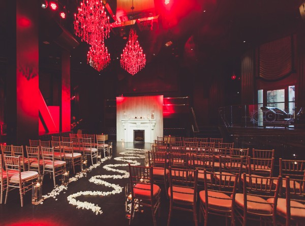 The ceremony was both romantic and ceremony, set with white rose petals, chiavari chairs and sexy red chandeliers. Photo by Adam Trujillo.