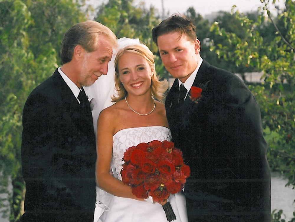 The bride with her father and her new husband.