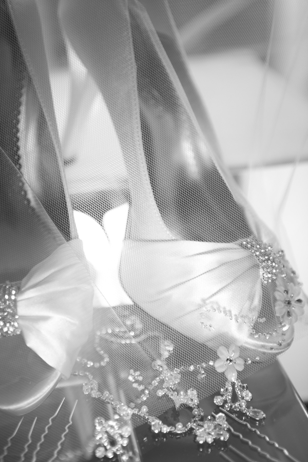 A tulle veil, crystal hair clips, and open toed bridal shoes were the perfect accessories to complete the feminine look.