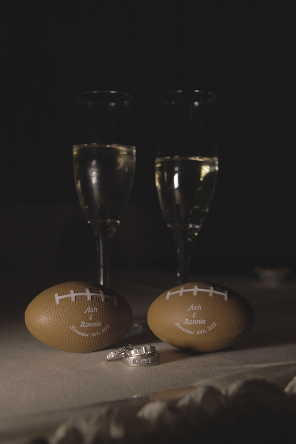 Toasting fluters, personalized mini football wedding favors, and the couples' rings.  Photo by www.altf.com.