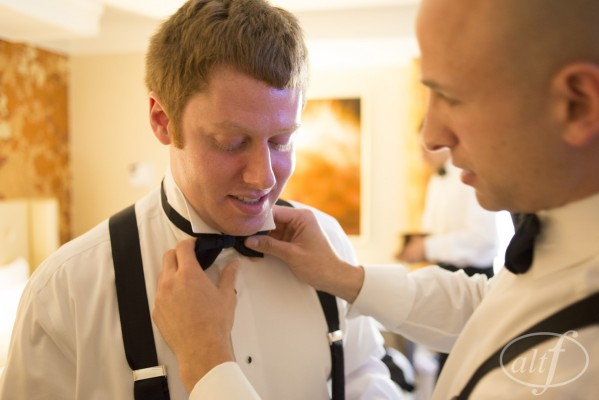 Groomsmen helping to straighten Jason's bow tie.