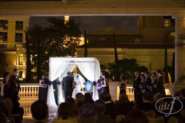 The Wedding Ceremony on the Grand Patio at Bellagio Las Vegass.  The white lights made the chuppah glow against the building.