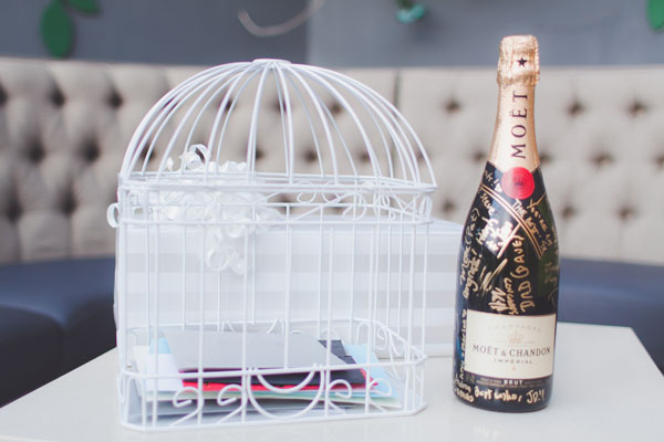 A birdcage collected the guests' gift cards, and a champagne bottle was set at the ready for guests to sign. Photo by Adam Trujillo.