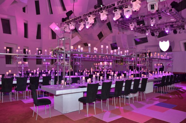 Long white banquet tables and black chairs look elegant in this architecturally unique wedding space.