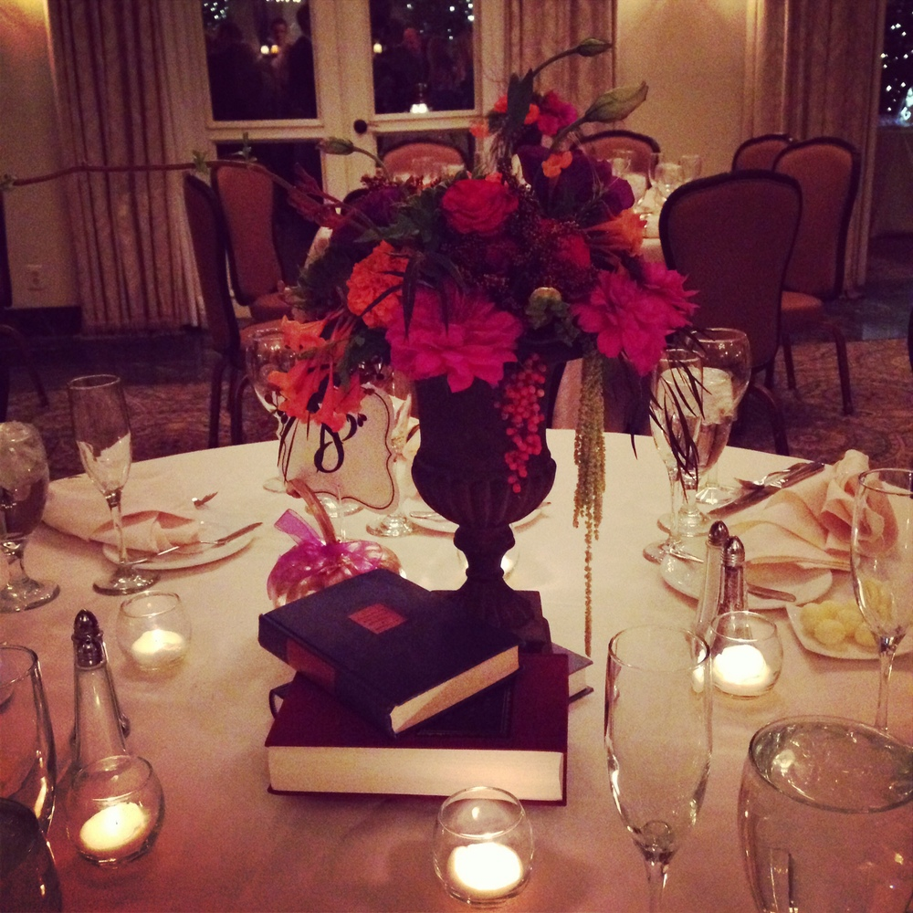 The centerpieces incorporated books (from their meeting and engagement photos) with vintage vases and jewel toned flowers.