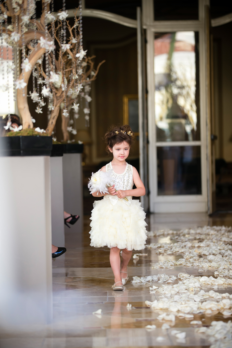 Our flower girl was more like a flower fairy, with a feather and rose wand that was a perfect match to her tiered and golden wreath headband.   Wedding Venue: Bellagio Las Vegas.  Location: The Grand Patio.  Flowers & Decor by Naakiti Floral.  Photo by www.ronmiller.com.  Las Vegas Wedding Planner: Andrea Eppolito Events.