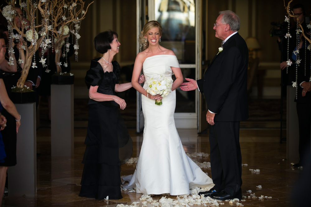 The Bride comes down the aisle, and met her parents half way there. Wedding Venue: Bellagio Las Vegas.  Location: The Grand Patio.  Flowers & Decor by Naakiti Floral.  Photo by www.ronmiller.com.  Las Vegas Wedding Planner: Andrea Eppolito Events.