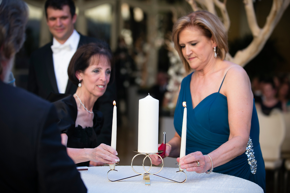 The mother of the bride and groom lit the tapes of the unity candle.   Wedding Venue: Bellagio Las Vegas.  Location: The Grand Patio.  Flowers & Decor by Naakiti Floral.  Photo by www.ronmiller.com.  Las Vegas Wedding Planner: Andrea Eppolito Events.