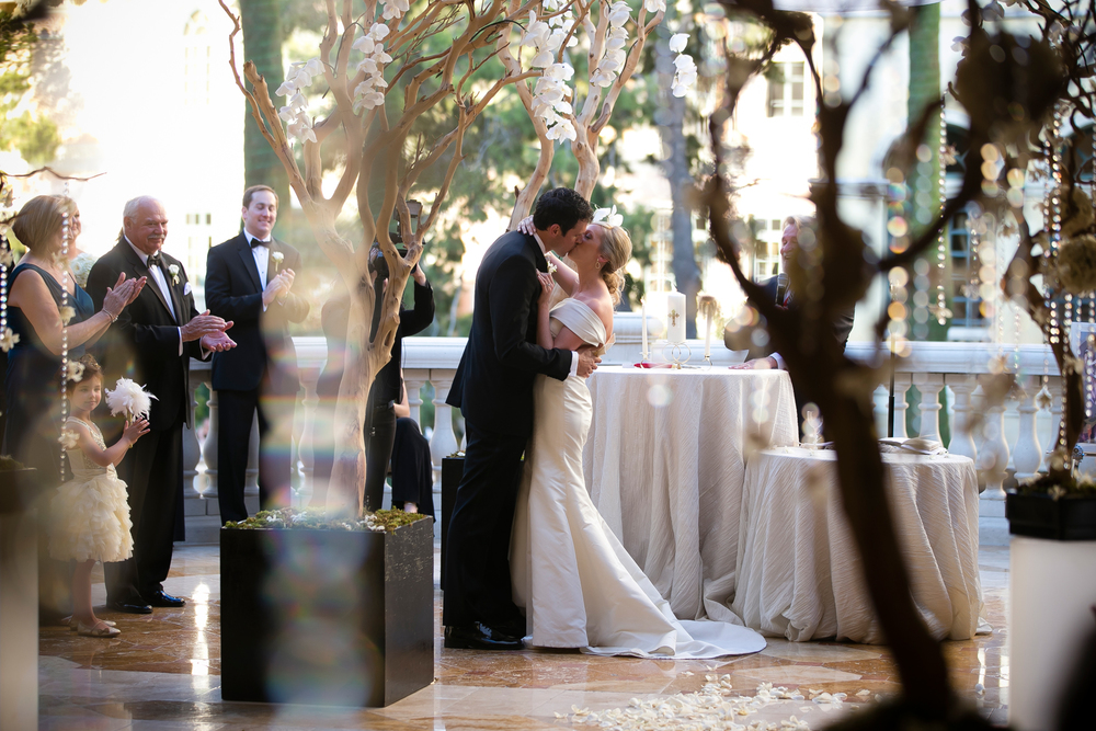 The last first kiss.... Wedding Venue: Bellagio Las Vegas.  Location: The Grand Patio.  Flowers & Decor by Naakiti Floral.  Photo by www.ronmiller.com.  Las Vegas Wedding Planner: Andrea Eppolito Events.