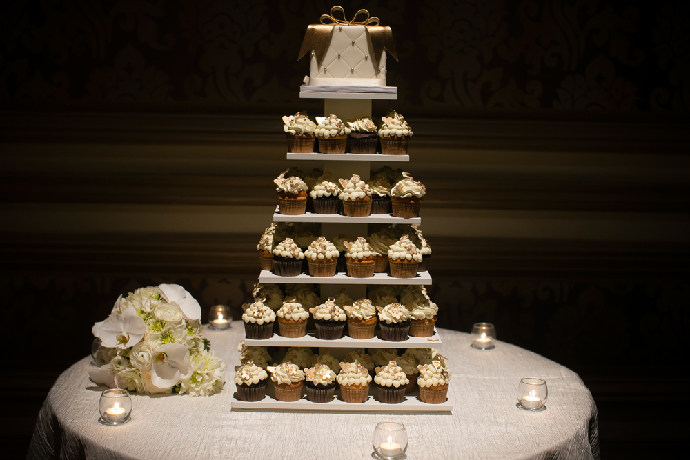 The cupcake tower was topped with a small wedding cake for the traditional cutting.    Wedding Venue:  Bellagio Las Vegas.   Photo by  www.ronmiller.com .  Las Vegas Wedding Planner:  Andrea Eppolito Events .