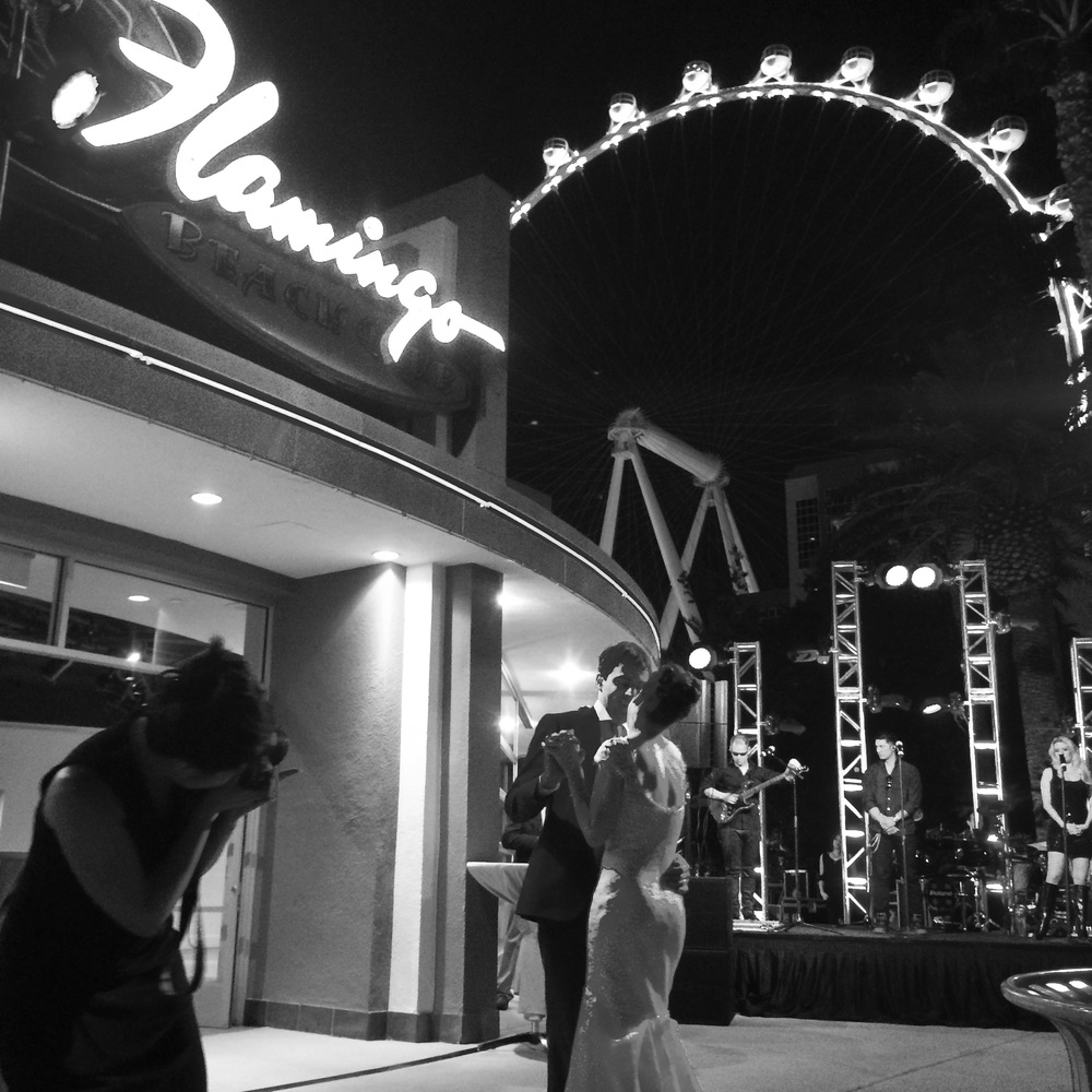 "Lindsey & Lockhart shared their first dance to ""Where is my mind?"" by The Pixies.  I love this photo!  Perfectly Vegas with the Flamingo sign and the new High Roller in the background.  A great mix of vintage and modern.  The black and white makes it just moody enough to be cool!  Notice Corry Arnold shooting in the corner.   Photo Courtesy of  Andrea Eppolito's Instagram."