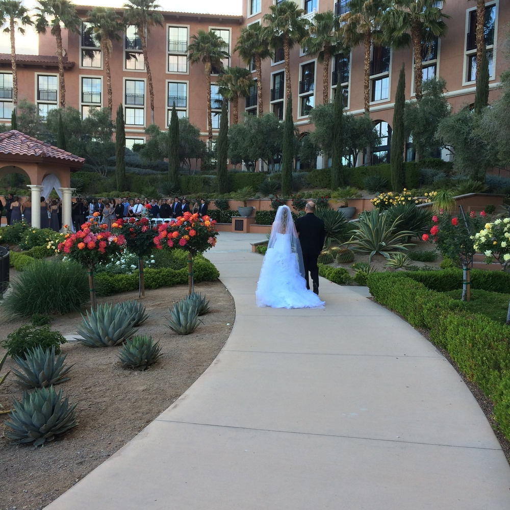 Amy was walked down the aisle by her father to the love theme from Twilight.   Las Vegas Wedding Planner: Andrea Eppolito | Wedding Venue: Westin Lake Las Vegas | Wedding Dress: Cosmobella | Floral and Decor: Naakiti Floral