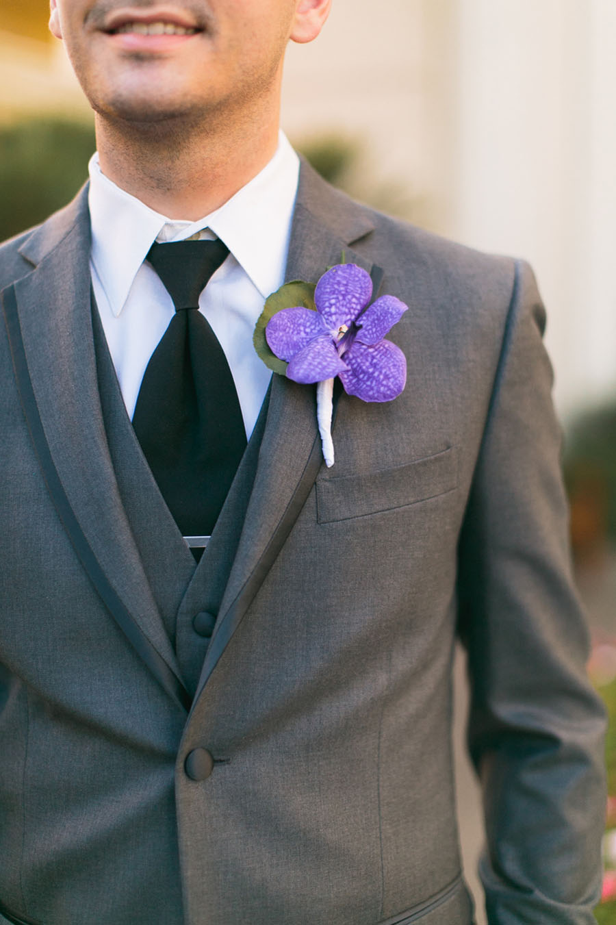 The Groom's grey Vera Wang tuxedo was accented with a deep purple orchid boutonniere.  Las Vegas Wedding Planner Andrea Eppolito.  Wedding at Four Seasons.  Photography by Meg Ruth.  Floral and Decor by Naakiti Floral.