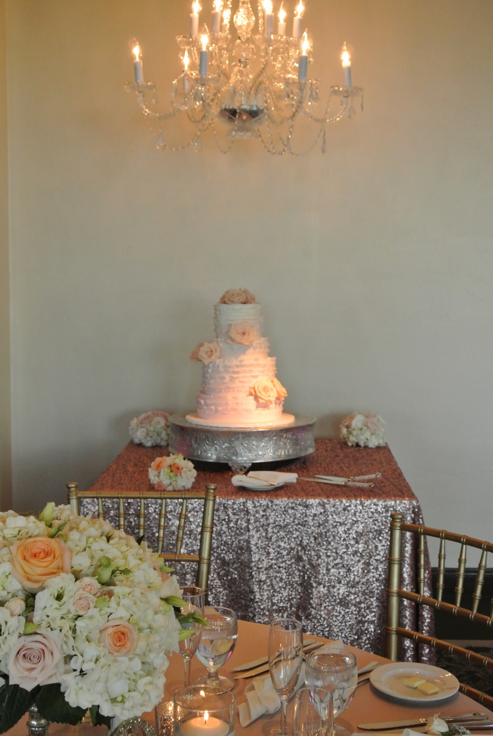 The Wedding Cake sat under a chandelier on sequence New Yorker glitter linen, and had the slightest whisper of ombre to it.  Photo by Andrea Eppolito. Las Vegas Wedding Planner Andrea Eppolito | Las Vegas Venue: Siena Golf Course |  Floral & Decor: Naakiti Floral and Sit On This