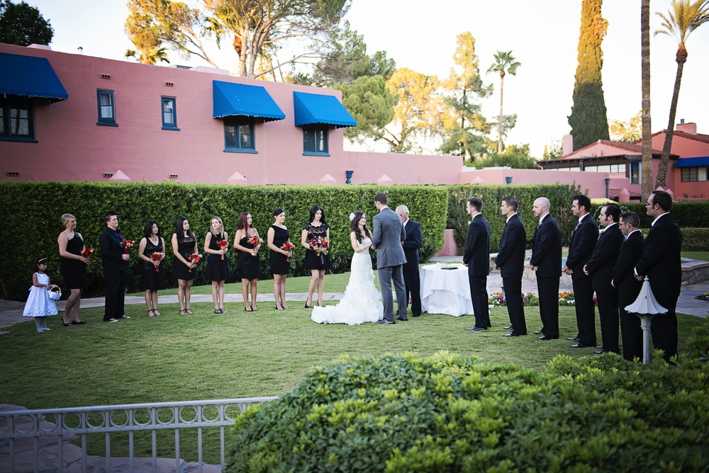The bridal party surrounded the bride and groom on the lawn in front of the stone fountain.    Destination Wedding Planner:   Andrea Eppolito Events   |  Historical Wedding Venue:   The Arizona Inn   |  Photography:  Raylene Streuber