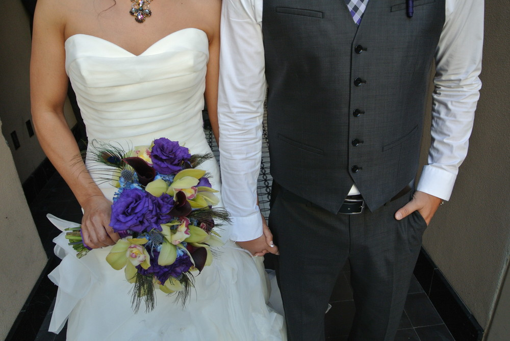 "The bride's bouquet featured jade green cymbidium orchids, purple flowers, and peacock feathers.  The groom was dapper and showed off his ""swag"" by forging a jacket and working a sharp vest!  Photo by Las Vegas Wedding Planner Andrea Eppolito."
