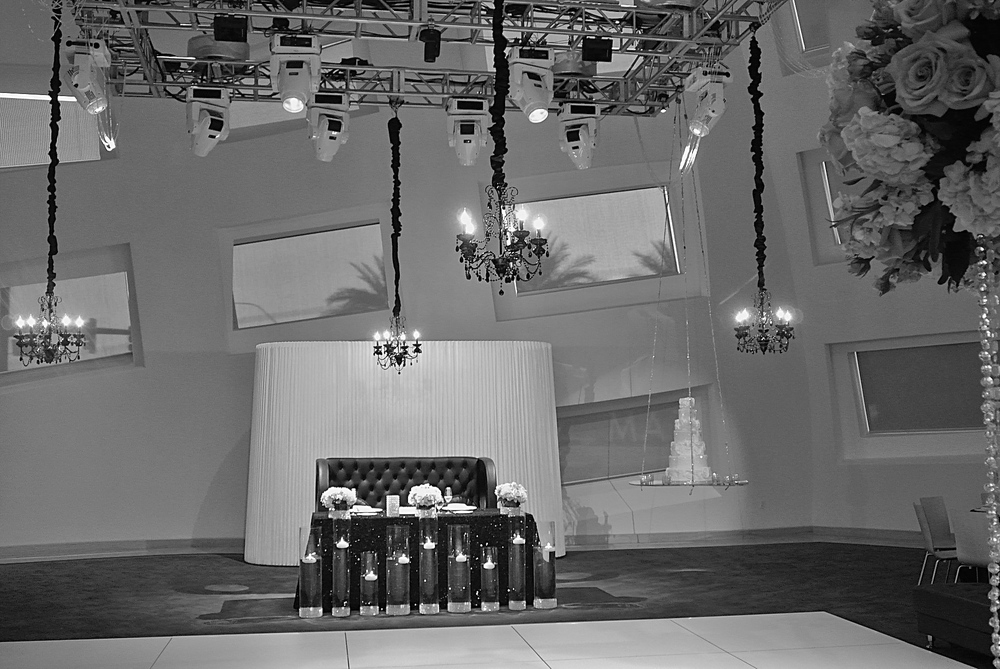 Black and White - Because it's gorgeous!  A white dance floor, black sparkle linens, candle light, Black crystal chandeliers, and a crystal encrusted floating cake.  Installation by Naakiti Floral and Sit On This Chair.    Las Vegas Wedding Planner Andrea Eppolito  |  Wedding at Keep Memory Alive Center  |  Floral and Decor by Naakiti Floral  |  Wedding Dress: Mina Olive | Wedding Cake: Peridot Sweets