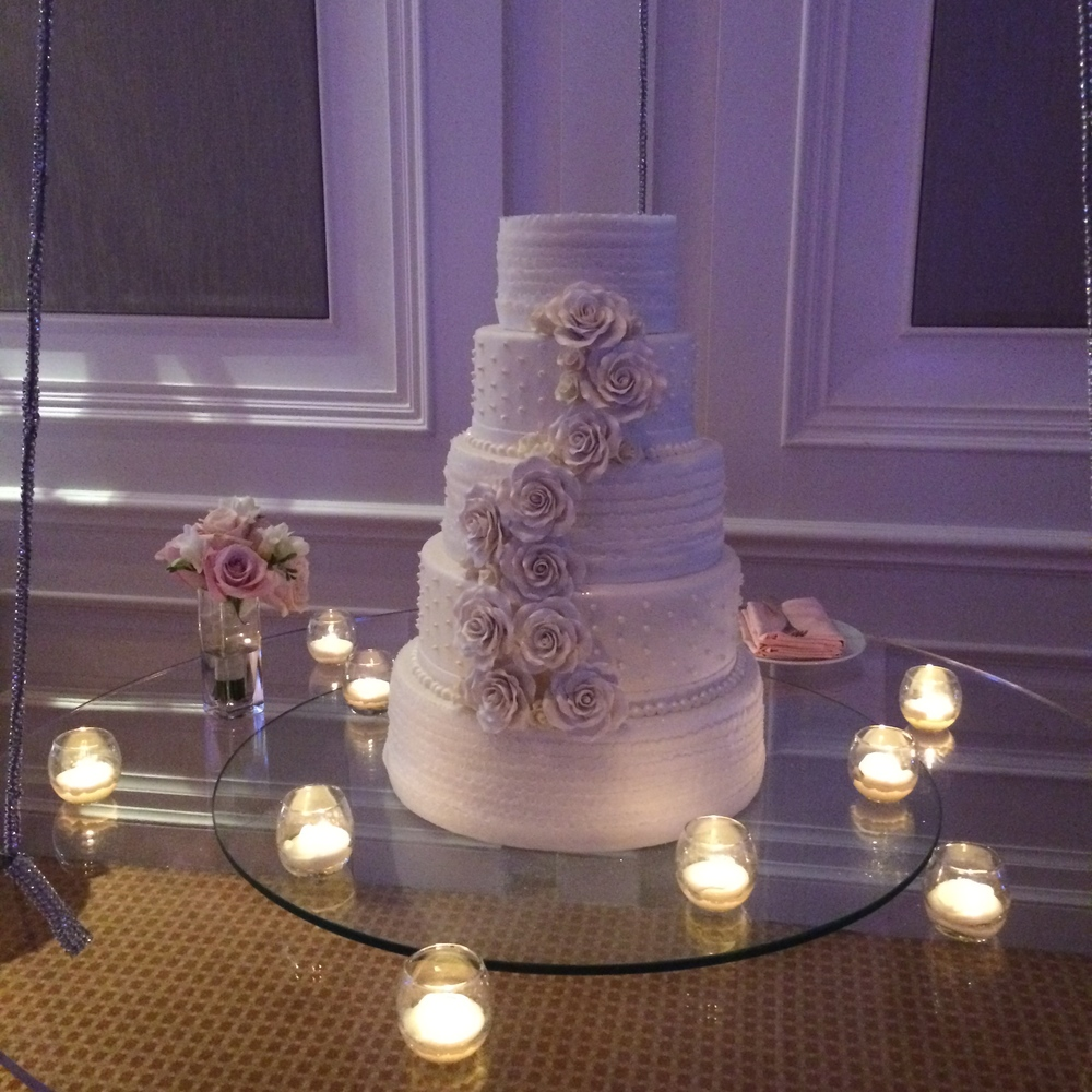 The five tiered hanging wedding cake was created by The Four Seasons and  featured sugar roses and pearl accents.