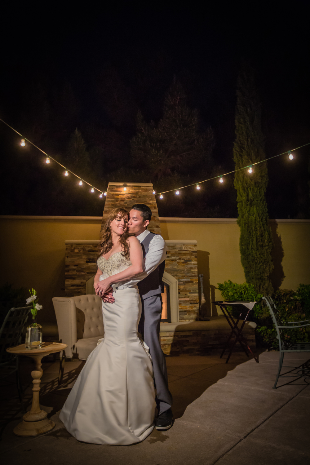 Newlyweds enjoying a quite moment by the fire place, under the bistro lighting. Las Vegas Wedding at Siena Golf Club  |  Photography by Ella Gagiano  | Floral and Decor by Naakiti Floral  |  Las Wedding Planner Andrea Eppolito