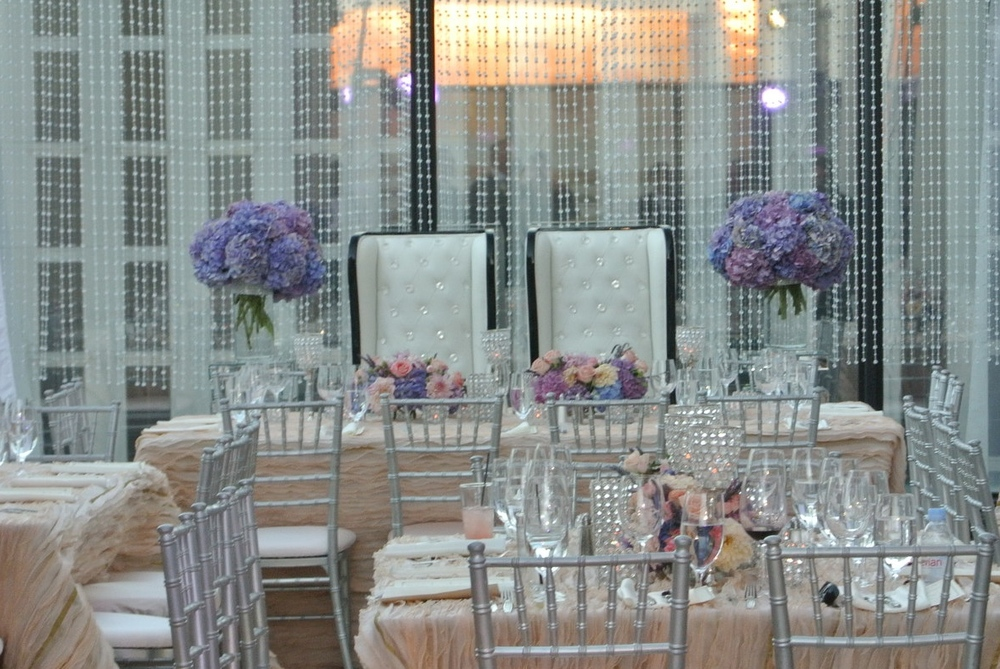 Megan's wish for a modern day fairytale was complete with amazing, wavy blush linens, platinum chiavari chairs, and flowers in purples, pinks, lavenders, and blue.  Alan hand selected the king and queen chairs without Megan's knowledge, the black trim adding a touch of masculinity to the decidedly feminine space.   Las Vegas Wedding Planner:   Andrea Eppolito Events    |  Las Vegas Wedding Venue:    Caesars Palace    |  Floral and Decor:    Naakiti Floral & Sit On This    |  Wedding Gown:   Pnina Torna  i   |  Behind the Scenes Photos:    Andrea Eppolito