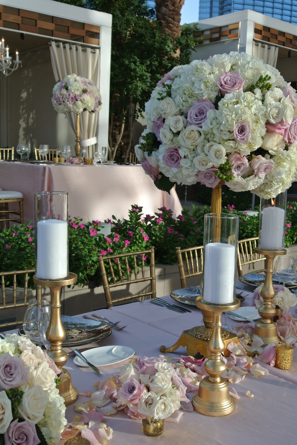 Long Banquet Tables were dressed in blush linens and topped with lush florals, high and low arrangements, and gold candelabras.   Las Vegas Wedding Planner:    Andrea Eppolito Events    |  Wedding Venue:    Mandarin Oriental Las Vegas      | Decor:    Naakiti Floral