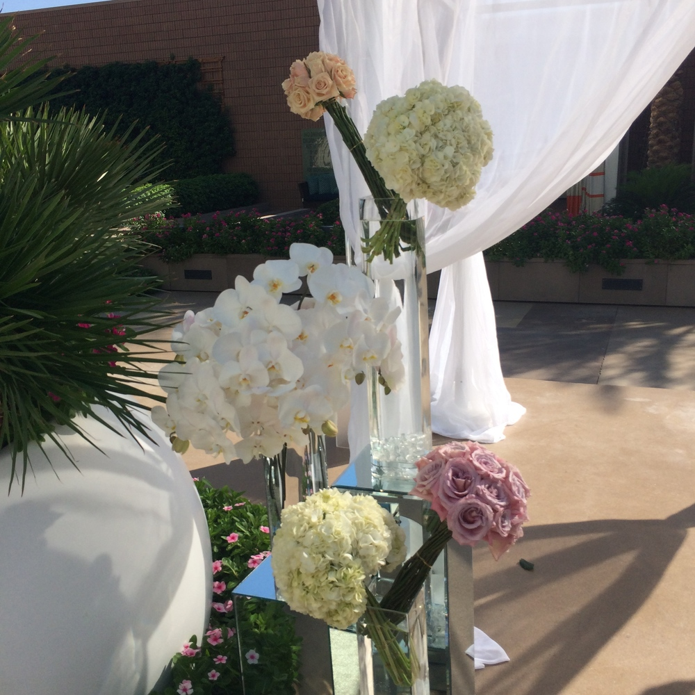 Naakiti Floral  created a breathless display at the couple's ceremony gazebo, with glass pedestals topped with clear vases and bundles of hydrangea, orchids, and roses.   Las Vegas Wedding Planner:    Andrea Eppolito Events    |  Wedding Venue:    Mandarin Oriental Las Vegas