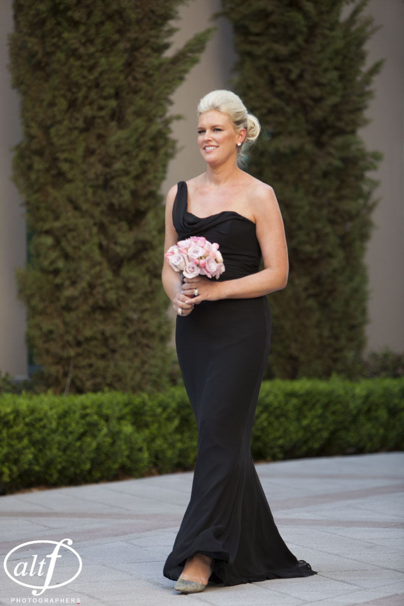 Maid of Honor in Black Amsale gown. Pink bouquet and black dress.