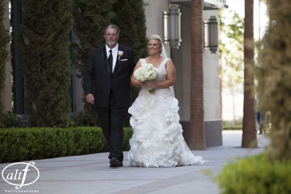 Bride being walked down the aisle in a custom wedding gown in Las Vegas.