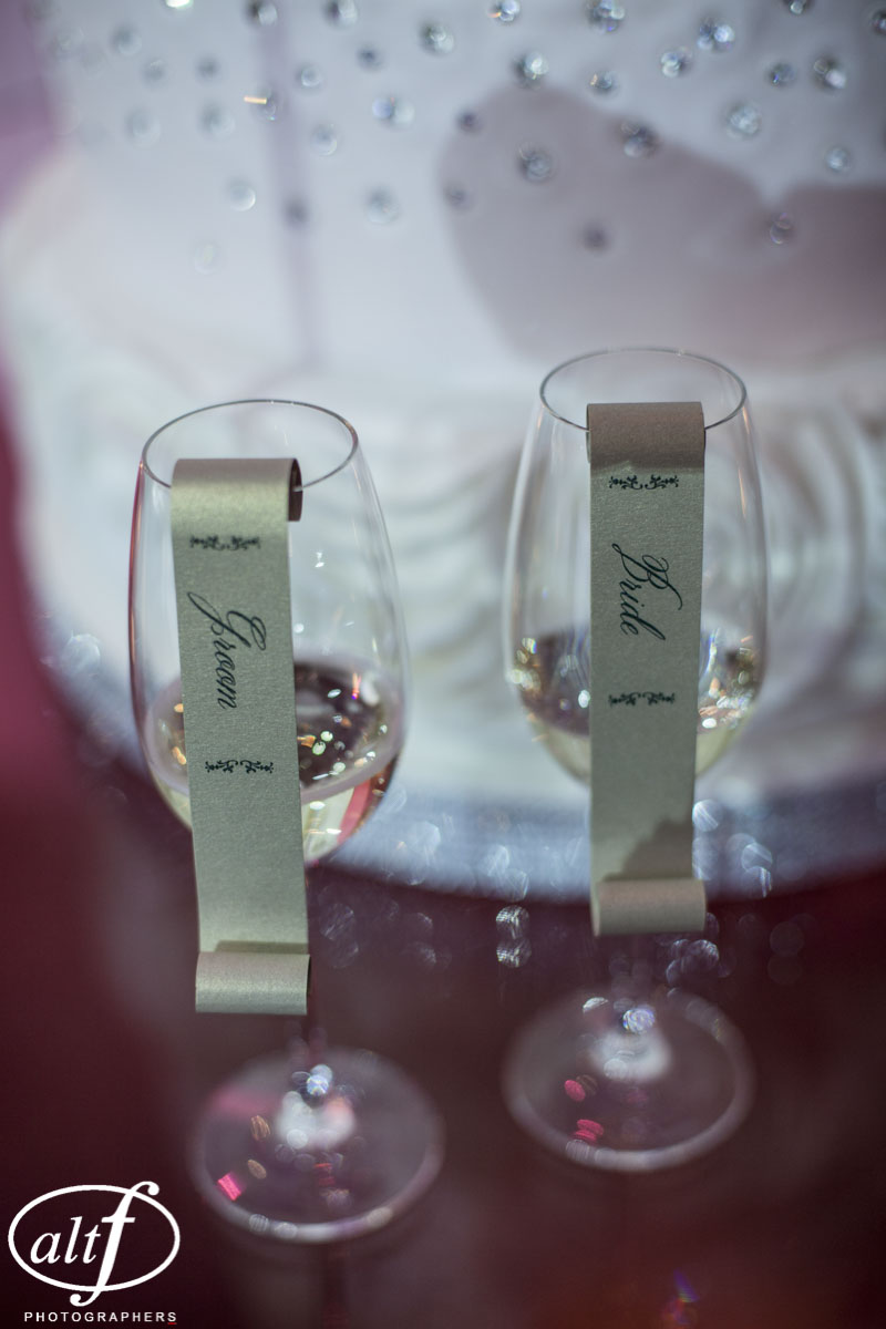 Golden Scrolls hung from Champagne Glasses and served as escort cards. Luxury wedding touched. Personalized wedding decor.