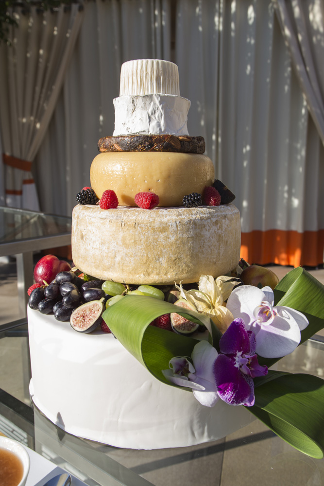 Who says that your cake has to be made of sugar and flower?!?  For the groom who loves cheese, we put together a cheese wheel wedding cake decorated with fresh fruits.  Cheese Cake by The Mandarin Oriental.  Photo by  Alt F Photography .