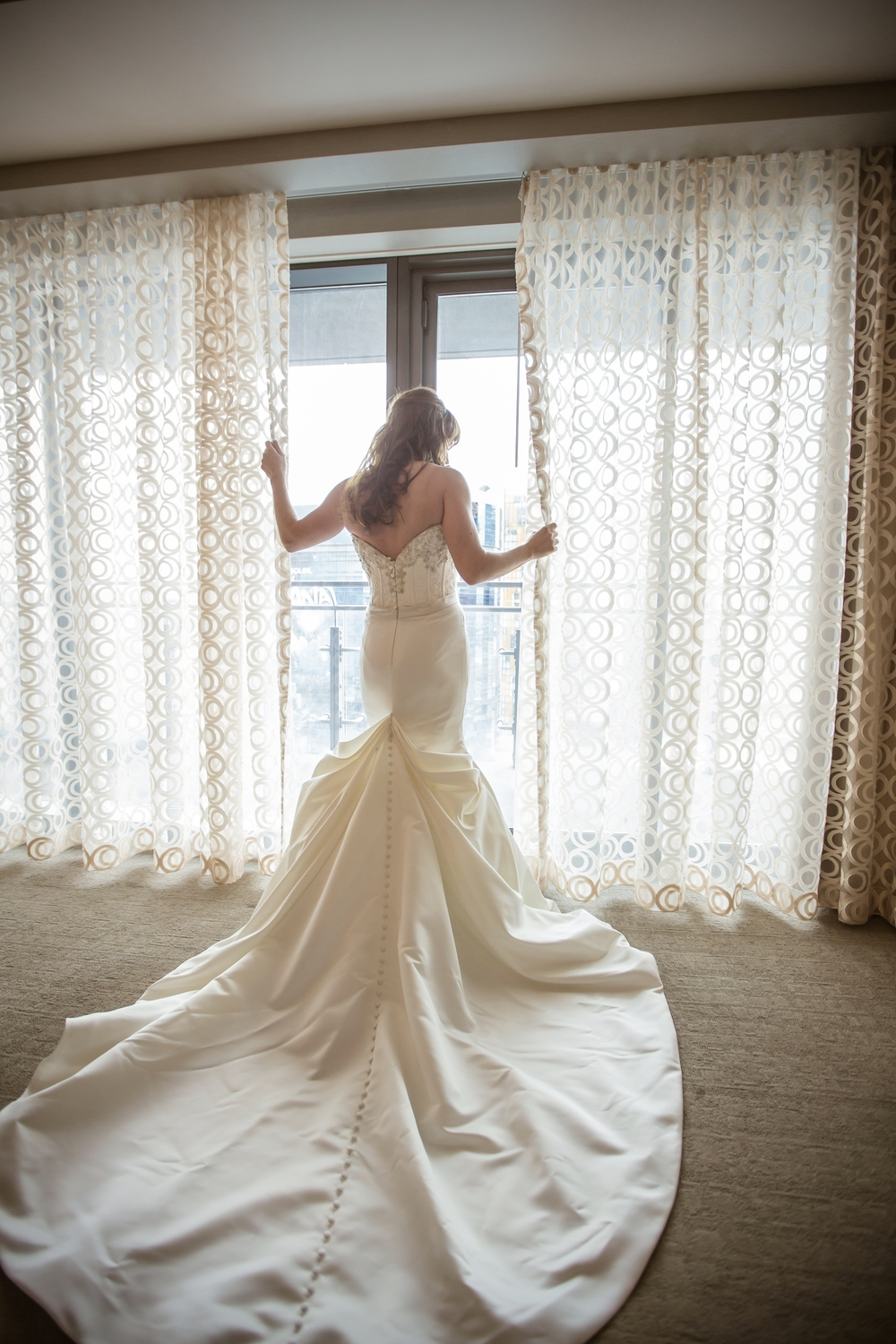 There was no other dress for this bride, who loved the long line of buttons that ran the entire length of the train.  I thought the lines of the back were brilliant, and that the pleating at the base of the train was both architectural and romantic.   Michelle Tran.  April 2014.  Photo by Elle Gagiano.